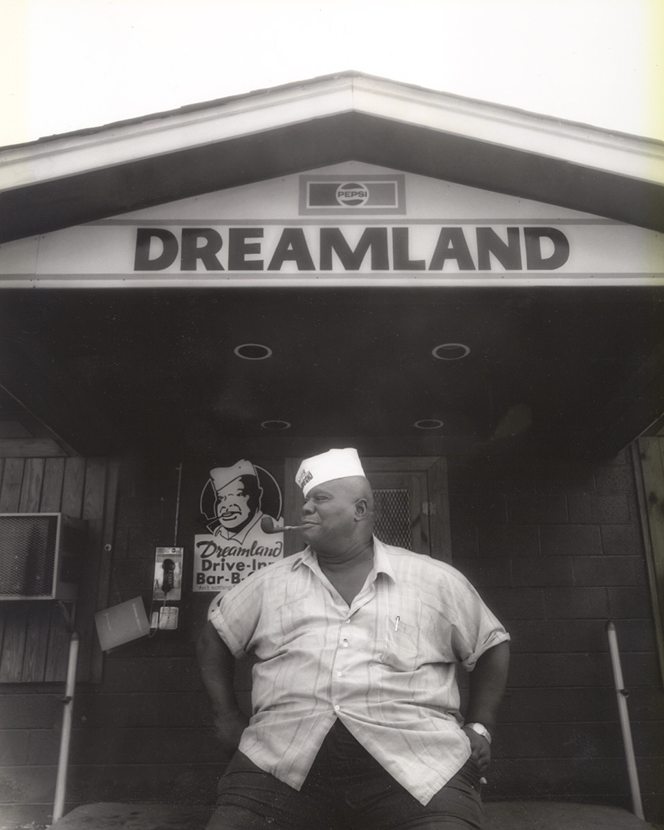 "Founder John ""Big Daddy"" Bishop sitting in front of the Tuscaloosa Dreamland BBQ"